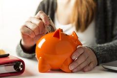 Vrouw die dollarrekening opnemen in een spaarvarken thuis in livin stock foto