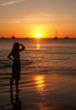 Vrouw die door de het plaatsen zon wordt aangestoken Stock Afbeelding
