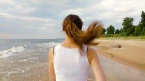 Vrouw die door de overzeese kustlijn op mooie avond lopen stock video
