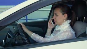 Vrouw die door de telefoon in de auto spreken stock videobeelden