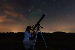 Vrouw die door een telescoop kijken die op de sterren letten royalty-vrije stock afbeeldingen