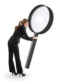 Vrouw die door een vergrootglas kijkt stock fotografie