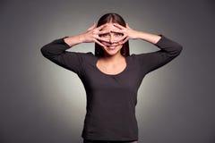 Vrouw die door haar vingers kijken stock afbeelding