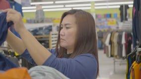 Vrouw die door kleren kijkt stock footage