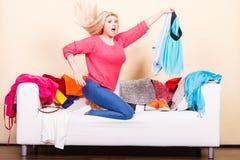 Vrouw die door kleren op slordige laag kijken Stock Foto's