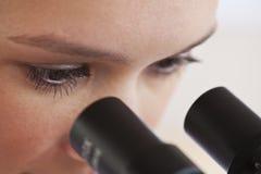 Vrouw die door microscoop kijkt royalty-vrije stock foto