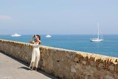 Vrouw die door overzees fotografeert stock foto's