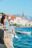 Vrouw die door Perast stad lopen De vakantie van de zomer Overzeese baai stock foto