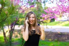 Vrouw die door smartphone spreken en duimen in de lentepark tonen Stock Foto's