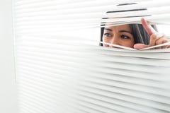 Vrouw die door sommige vensterzonneblinden gluren Stock Afbeelding