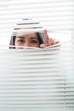 Vrouw die door sommige vensterzonneblinden gluren Royalty-vrije Stock Foto