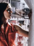 Vrouw die door venster, het ontspannen kijken stock fotografie