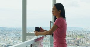 Vrouw die door venster kijken terwijl het hebben van kop van koffie 4k stock videobeelden
