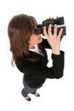 Vrouw die door verrekijkers kijkt Stock Foto's