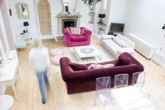 Vrouw die door woonkamer loopt Stock Afbeeldingen