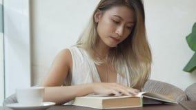 Vrouw die door woordenboek en het drinken koffie kijken stock video