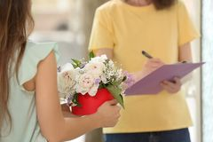 Vrouw die doos met mooie pioenbloemen ontvangen van koerier royalty-vrije stock afbeelding