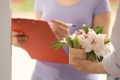 Vrouw die doos met mooie pioenbloemen ontvangen van koerier stock fotografie