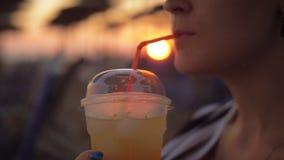 Vrouw die drank op het strand hebben bevroren bij zonsondergang stock video