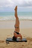 Vrouw die driepoot headstand op strand doen Stock Afbeeldingen