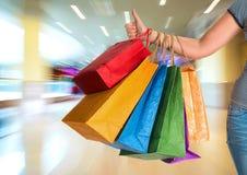 Vrouw die duim tonen en het winkelen zakken houden Stock Foto's