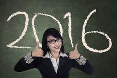 Vrouw die duimen met nummer 2016 tonen Stock Afbeeldingen