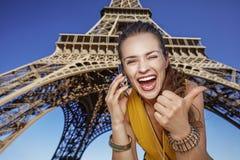 Vrouw die duimen tonen en op mobiele telefoon in Parijs spreken Stock Afbeeldingen