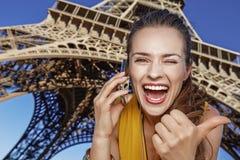 Vrouw die duimen tonen en op mobiele telefoon in Parijs spreken Stock Fotografie