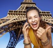 Vrouw die duimen tonen en op mobiele telefoon in Parijs spreken Royalty-vrije Stock Foto