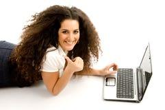 Vrouw die duimen toont en aan laptop werkt Stock Afbeeldingen