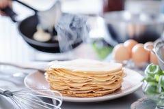 Vrouw die dunne pannekoeken op pan in keuken maken royalty-vrije stock fotografie