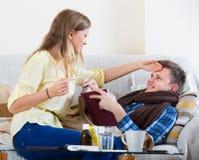 Vrouw die echtgenoot met verwarmingspijp behandelen stock fotografie