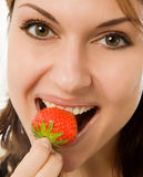 Vrouw die een aardbei eet Stock Afbeelding