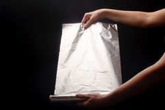 Vrouw die een aluminiumfolie houdt Royalty-vrije Stock Afbeeldingen