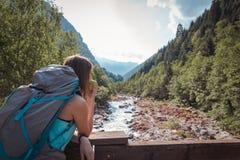 Vrouw die die een appel op een brug eten door bergen wordt omringd royalty-vrije stock foto