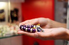 Vrouw die een armband in een juwelenopslag neemt stock fotografie