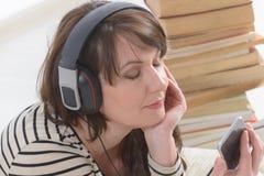 Vrouw die een audiobook luisteren royalty-vrije stock foto's