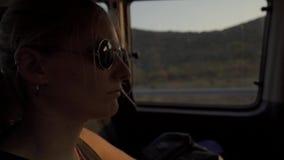 Vrouw die in een auto bij zonsondergang reizen stock footage