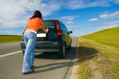 Vrouw die een auto duwt Stock Afbeeldingen
