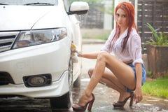 Vrouw die een auto wassen stock afbeeldingen