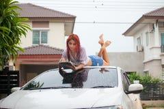 Vrouw die een auto wassen stock afbeelding
