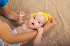Vrouw die een baby kleden stock afbeelding