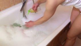 Vrouw die een bad met warme water en bellen in werking stellen stock footage