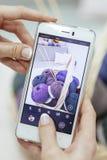 Vrouw die een beeld met haar telefoon van haar kleinhandels online winkel nemen royalty-vrije stock afbeeldingen