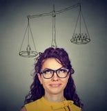 Vrouw die een besluit met schaal boven hoofd en mensen op een saldo nemen royalty-vrije stock afbeeldingen