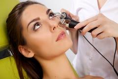 Vrouw die een bevorderende gezichtsbehandeling van een therapeut hebben Stock Afbeeldingen