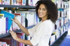 Vrouw die een bibliotheekboek trekt van plank Stock Foto's