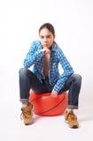 Vrouw die in een blauw overhemd en jeans op de bal zitten Royalty-vrije Stock Afbeelding