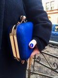 Vrouw die een blauwe handtas in haar hand houden stock foto