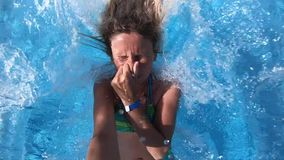 Vrouw die in een blauwe waterpool springen stock videobeelden